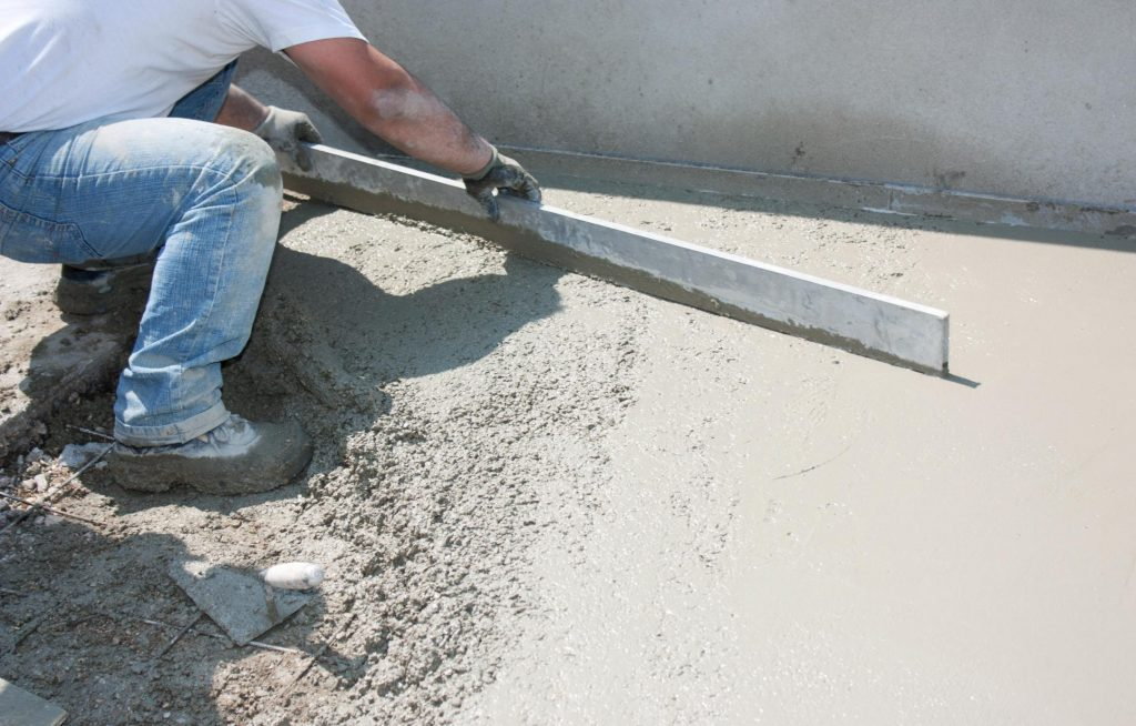 man leveling the cement
